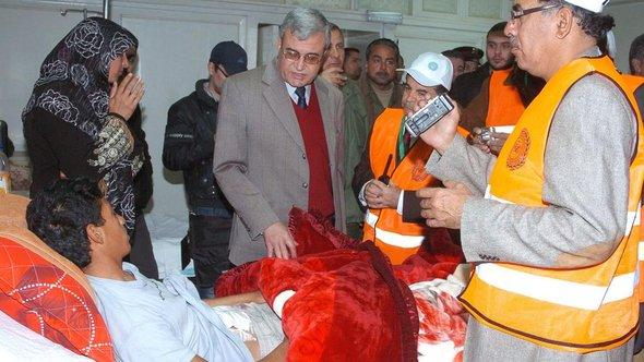 Arab League observers (wearing orange jackets) checking wounded people in the national hospital in Daraa, southern Syria in December 2011 (photo: EPA/SANA Handout)