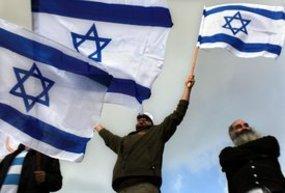 Jewish settlers waving Israeli flags (photo: dpa)