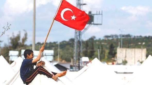 A Syrian boy holds up a Turkish national flag (photo: Reuters)
