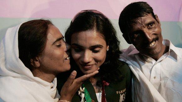 Pakistans Läuferin Naseem Hameed (m.) mit ihrer Mutter und ihrem Vater; Foto: AP