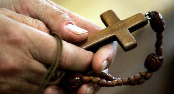 Hand mit Rosenkranz; Foto: picture-alliance/dpa
