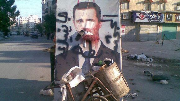 Ein Poster von Bashar al-Assad neben Mülltonnen in Aleppo; Foto: Reuters