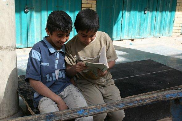 Zwei Jungen lesen ein Buch, al-Mutanabbi-Straße in Bagdad; Foto: Munaf al-Saidy