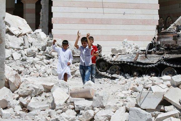 Kinder spielen auf einem Trümmerfeld vor einer Moschee und einem zerstörten Panzer in Azaz; Foto: Joshua Archer
