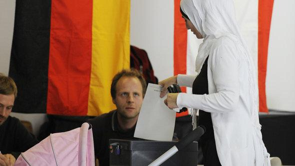 A Muslim woman wearing a headsacrf at the ballot box during Germany's parliamentary election in 2009 (photo: picture-alliance/dpa) (photo: picture-alliance/dpa)