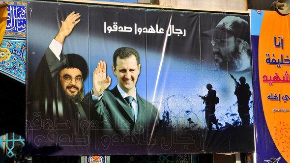 Hisbollah-Chef Nasrallah und Assad auf einem Plakat im schiitischen Pilgerort Sayyida Zainab, Foto:picture alliance/ZB