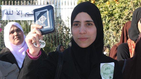 Tunesische Islamistin mit einem Aufkleber: Ja zur Scharia und einer Ausgabe des Korans in der Hand, Foto: DW
