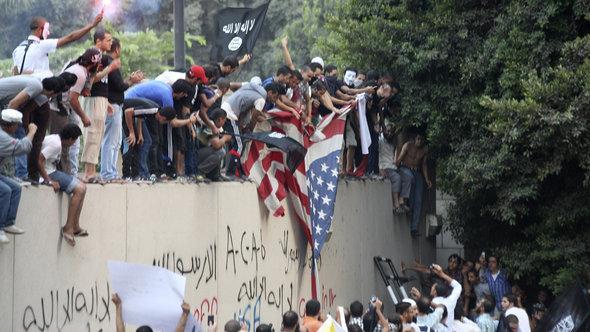 Demonstranten auf der Mauer der US-Botschaft in Kairo; Foto: dapd