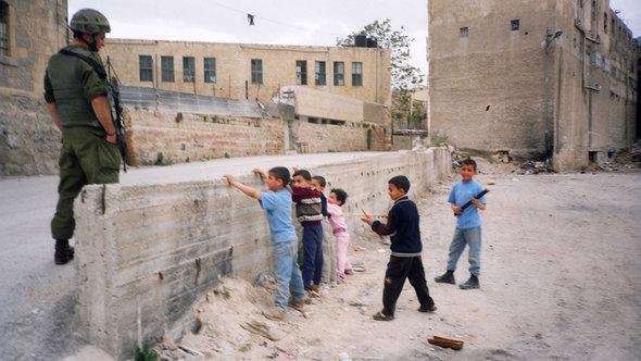 Ausstellungsexponat - Palästinensische Kinder spielen eine Checkpoint-Kontrolle vor einem israelischen Soldaten der IDF; Foto: © Breaking the Silence