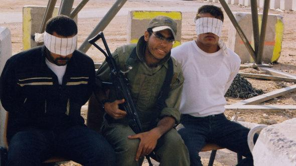 An Israeli soldier posing with blindfolded Palestinian prisoners (photo: © Breaking the Silence)