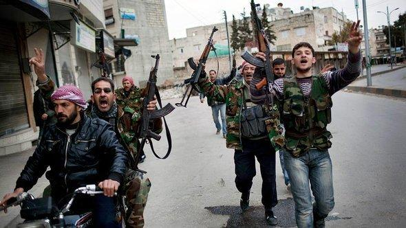 Free Syrian Army fighters celebrate after hearing that their comrades destroyed a Syrian Army tank in Idlib, north Syria (photo: AP)