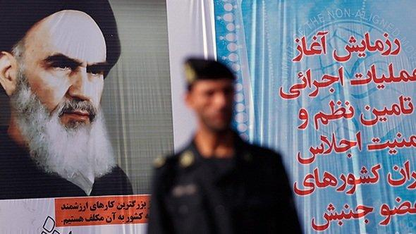 An Iranian policemen and a larger-than-life poster of