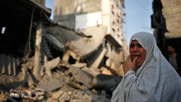 Eine palästinensische Frau steht vor ihrem zerstörten Haus in Gaza-Stadt; Foto: Reuters/Mohammed Salem