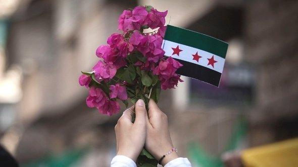 Frau hält Fahne der Freien Syrischen Armee sowie einen Blumenstrauß; Foto: AP