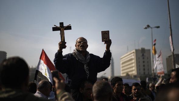Auf einer Demonstration gegen die Macherweiterung Mursis hält ein Mann Koran und Kreuz in die Höhe, Tahrir-Platz in Kairo, 30. November; Foto: AFP Photo/Gianluigi Guercia