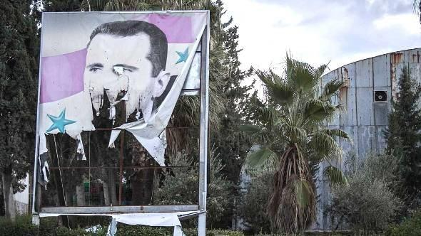 A damaged poster of Bashar al-Assad in Aleppo on 8 December 2012 (photo: Narciso Contreras/AP/dapd)