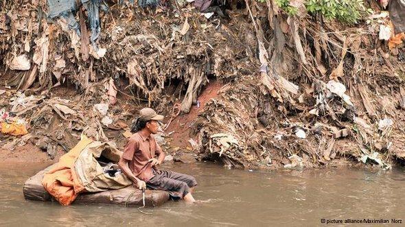 Leben im Müll am Fluss Ciliwung in Jakarta. Mann fischt auf Müllfloß nach Müll; Foto:dpa