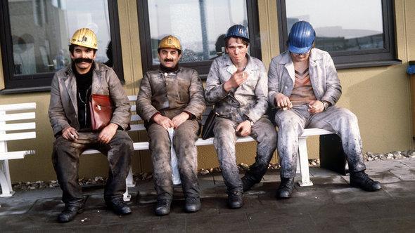 Türkische Gastarbeiter in sitzen nach ihrer Schicht auf einer Bank auf dem Gelände der Zeche Neu-Monopol in Bergkamen im Kreis Unna, Foto: dpa/picture-alliance