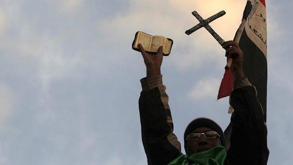 Ein Gegner Mohammed Mursis hält in Kairo vor dem Präsidentenpalast den Koran und ein Kreuz hoch; Foto: Reuters