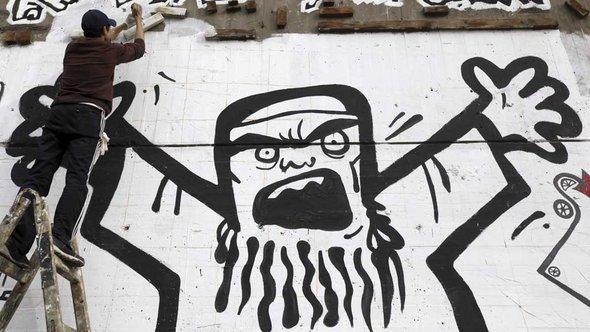 A man is spraying a Muslim Brotherhood caricature graffiti in Cairo (photo: Reuters)