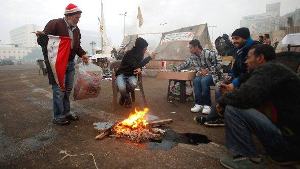 Protesters opposing Egyptian President Mohamed Morsi sit around a fire to warm themselves up at Tahrir Square in Cairo December 14, 2012 (photo: Reuters)