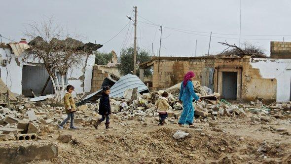 Syrische Zivilisten in einem zerstörten Dorf; Foto: DW/A. Stahl