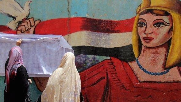 Ägypterinnen vor einem Graffiti und ausgehängten Kandidatenlisten für die anstehenden Präsidentschaftswahl in Kairo; Foto: dpa