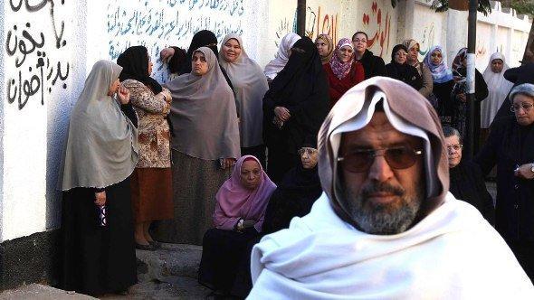 Frauen stehen neben einem regierungsfeindlichen Graffiti Schlange, Foto: Reuters/Stringer