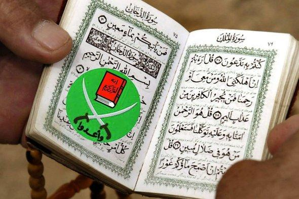 Mann liest Koran mit Symbol der Muslimbruderschaft als Lesezeichen; Foto: dpa