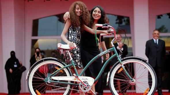 """Haifaa al-Mansour and Waad Mohammed pose with the bicycle from the film on the red carpet during the premiere screening of """"Wadjda"""" during the Venice Film Festival 2012 (photo: Reuters)"""
