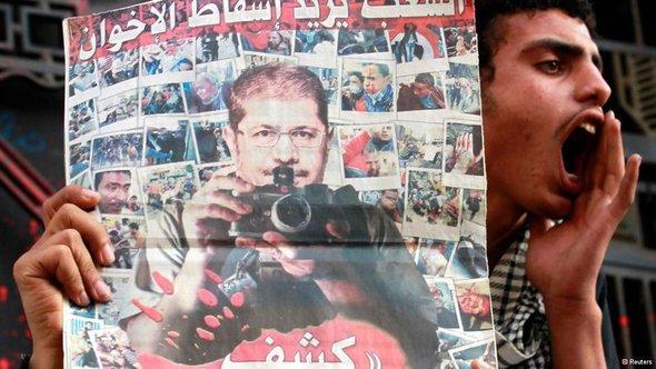 'Das Volk will den Sturz der Muslimbrüder!' - Demonstrant in Kairo hält ein Plakat gegen Präsident Mursi und die Muslimbruderschaft hoch; Foto: Reuters
