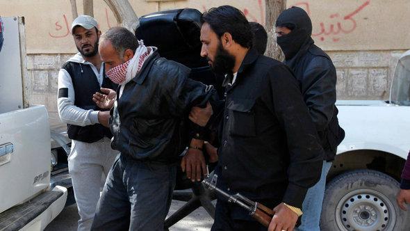 Kämpfer der Al-Nusra-Front mit einem Gefangenen in der Provinz Raqqa; Foto: Reuters/Hamid Khatib