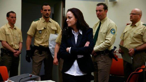 Beate Zschäpe mit Polizeibeamten im Gerichtssaal; Foto: Reuters
