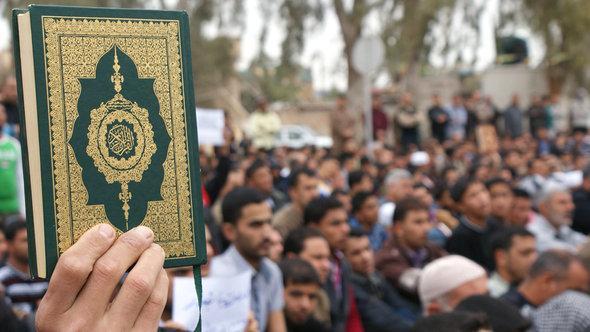 Islamisten im irakischen Bakuba halten den Koran hoch; Foto: Reuters
