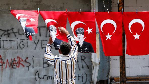 Demonstrant hängt türkische Fahnen mit dem Bild Atatürks auf; Foto: Reuters