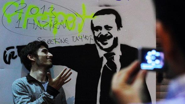 Aktivist vor Erdogan-Grafitti in Istanbul; Foto: Gaia Anderson