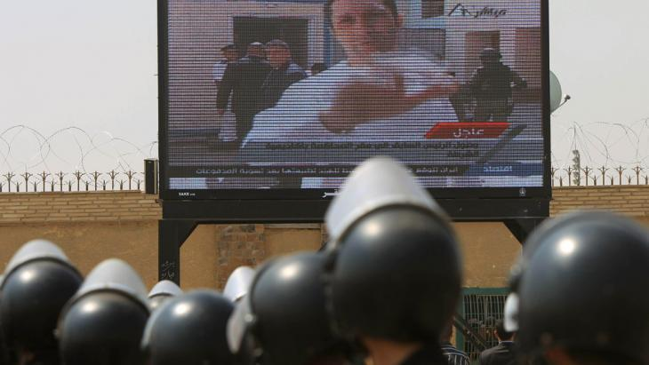 Ägyptische Polizei schaut auf einen TV-Sender, der über Alaa Mubarak, Sohn des Ex-Präsidenten Hosni Mubarak, berichtet; Foto: AFP/Getty Images