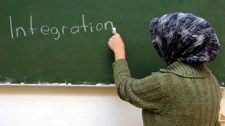 """Eine türkische Frau schreibt im Schulungsraum der interkulturellen Frauenbegegnungsstätte """"verikom"""" in Hamburg-Wilhelmsburg das Wort """"Integration"""" an die Tafel; Foto: dpa/picture-alliance"""