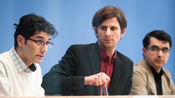 Elias Perabo (Mitte) gemeinsam mit den nach Deutschland geflohenen Aktivisten Hozan Ibrahim (l.) and Ferhad Ahma während einer Pressekonferenz in Berlin; Foto: picture-alliance/dpa