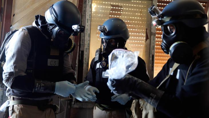 A U.N. chemical weapons expert, wearing a gas mask, holds a plastic bag containing samples from one of the sites of an alleged chemical weapons attack in the Ain Tarma neighbourhood of Damascus (photo: Reuters)