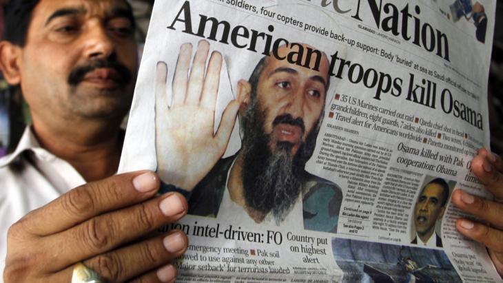 """Pakistaner liest Zeitung mit der Überschrift: """"Amerikanische Truppen töten Osama""""; Foto: picture-alliance/dpa"""