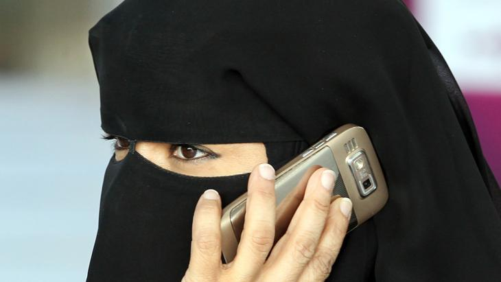 Woman wearing a niqab, talking over a mobile phone (phone: dpa/picture-alliance)