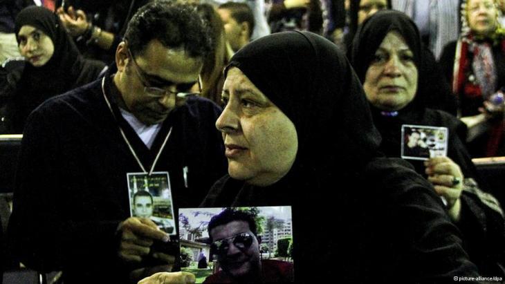 Angehörige der Opfer der Revolution halten Bilder der Toten.; Foto: picture-alliance/dpa