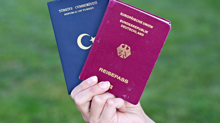 A hands holds up a Turkish and a German passport (photo: picture-alliance/dpa)