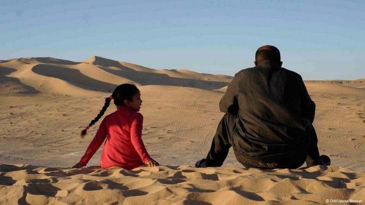 Ein Mann und ein Mädchen in der libyschen Wüste; Foto: Valerie Stocker/DW