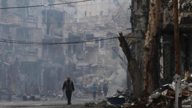 Ein Mann passiert eine zerstörte Straße in Deir al-Zor; Foto: Reuters