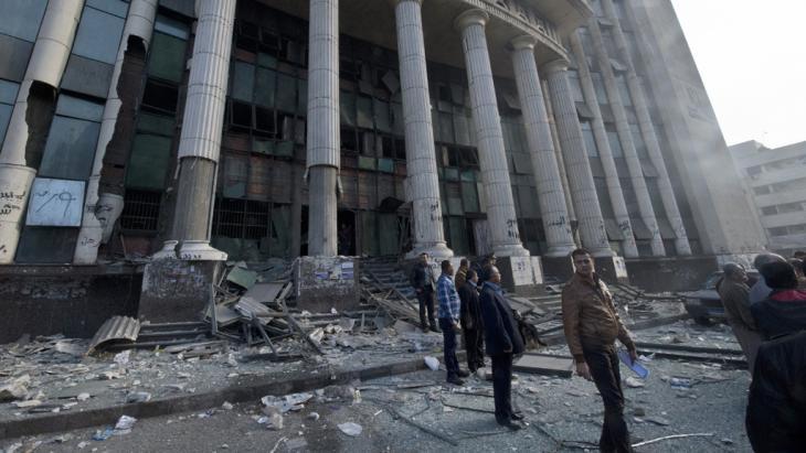 Ägypter stehen vor dem Gerichtsgebäude, auf das am Morgen der Wahl über eine neue ägyptischen Verfassung ein Anschlag verübt wurde, Kairo, 14. Januar 2014; Foto: Khaled Desouki/AFP/Getty Images
