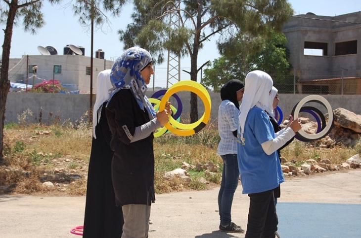Eine Gruppe Mädchen der Zirkusschule üben das Jonglieren mit Reifen; Foto: Palestinian Circus School)
