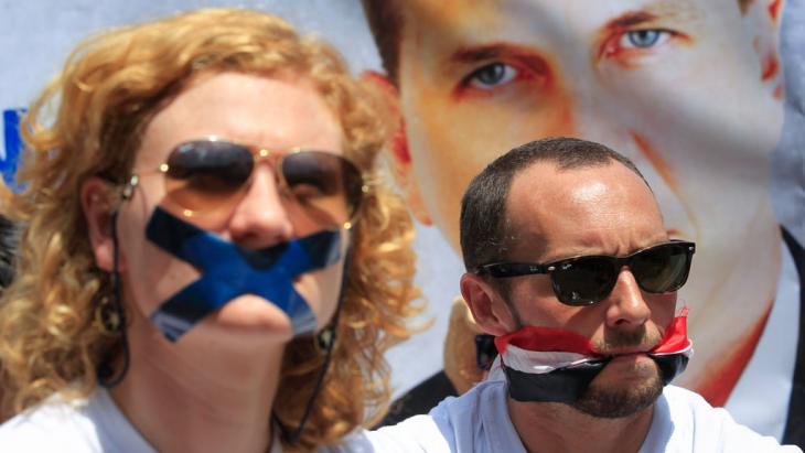 Journalists Phil Moore (rechts) und Jessica Hatcher protestieren gegen die Inhaftierung eines Mitarbeiters von Al-Dschasira English; Foto: picture-alliance/dpa