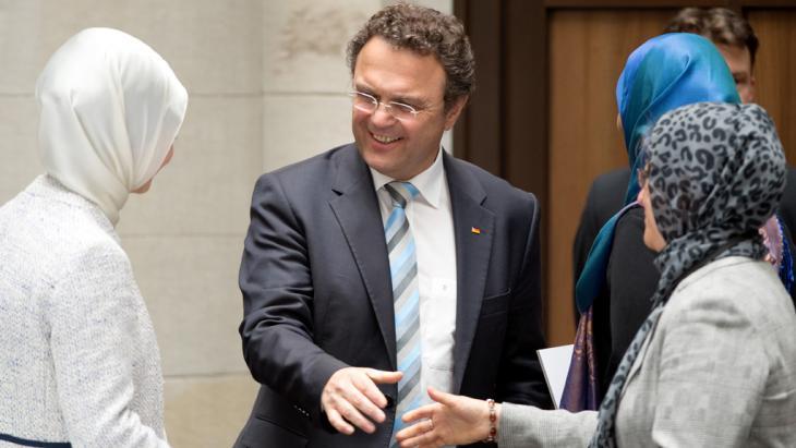 Der frühere Innenminister Hans-Peter Friedrich begrüßt Teilnehmerinnen der Deutschen Islamkonferenz; Foto: dpa/picture-alliance